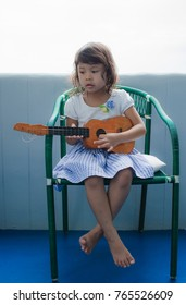 Asian Child Happy Play Ukulele In Room