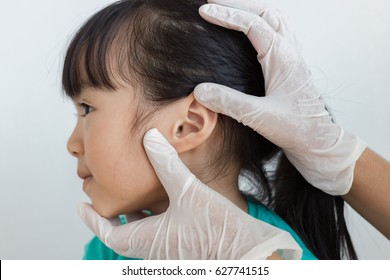asian child has ear check up by doctor