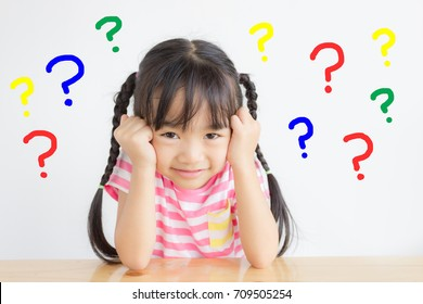 asian child has a headache with colorful question marks on white background