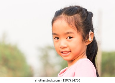 asian child with hearing aid can help her  to hear more clearly