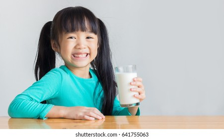 asian child hold a glass of milk and smile