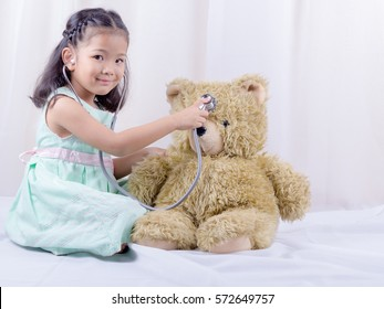 asian child holding Stethoscope, smiling And check teddy bear. The future of children, concept.