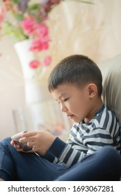 Asian child at home during lockdown, playing with smartphone