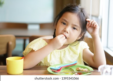 Asian child hungry or kid girl enjoy eating food by hand and sloppy with colorful plastic spoon and fork with dish for delicious and happy for lunch or breakfast in morning at restaurant or food court