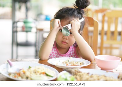 Asian child or kid girl anorexia or sad and bored food or boredom with sleepy vacant and prop up or hand to head with headache on wood table for breakfast or lunch eating at restaurant on preschool