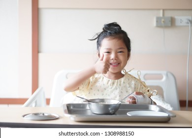 Asian child or kid girl Influenza A sick with happy smiling and show thumb to good encouragement with salt water in hand blood vessels on bed at hospital room for treatment healthcare with lunch food