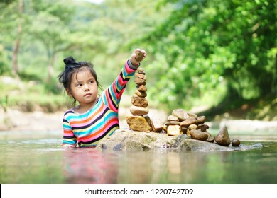 Asian child or kid girl learning sort or stack pebble stone tower or pyramid for water balance training and meditation with nature relax on summer holiday travel at stream or river in forest with tree