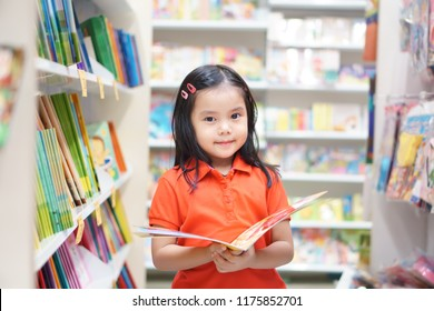 Asian child or kid girl red shirt happy smile and reading or choose tale or story book and shopping on bookshelf in bookstore or library room at kindergarten school or nursery learn for summer study