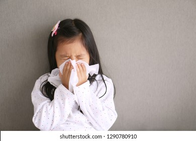 Asian child or kid girl sick with sneezing on nose and cold cough on tissue paper because weak or virus and bacteria from dust weather and kindergarten and pre school for medical background gray space