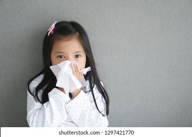 Asian child or kid girl sick and sad with sneezing on nose and cold cough on tissue paper because influenza and weak or virus and bacteria from dust weather and kindergarten school for medical BG