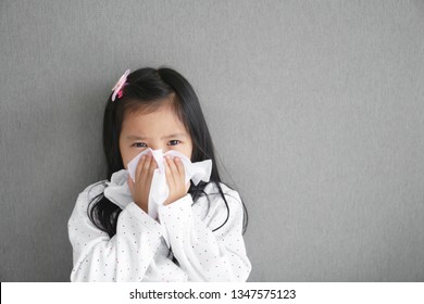 Asian child or kid girl sick and sad with sneezing on nose and cold cough on tissue paper because influenza and weak or virus bacteria from dust weather or smoke and kindergarten school for medical