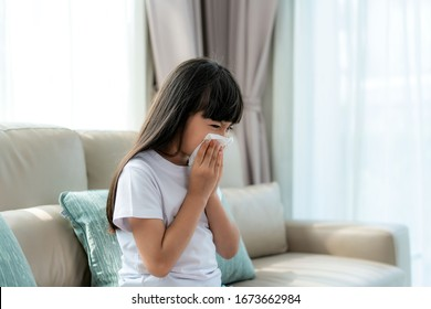 Asian child or kid girl sick and sad with sneezing on nose and cold cough on tissue paper because influenza and weak or virus bacteria