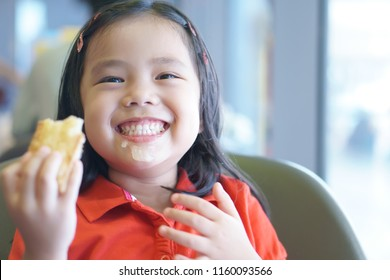 Asian child or kid girl smile and enjoy eating pineapple pie and sloppy mouth with happy fun for delicious snack or yummy dessert on holiday at cafe restaurant or coffee shop and wear red shirt