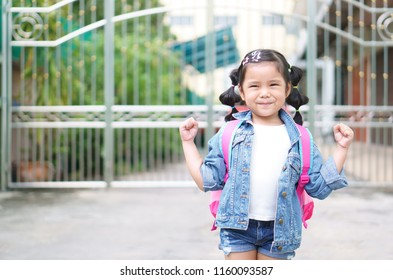 Asian child or kid girl smile and student shoulder schoolbag with happy and show handful for strong healthy and confident go to school or back to school and kindergarten on summer study or learning