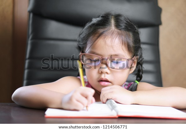 asian child or kid girl wear eye glasses for short sighted and diligent with enjoy doing homework or learning writing on white paper book and desk or table at preschool nursery or kindergarten office