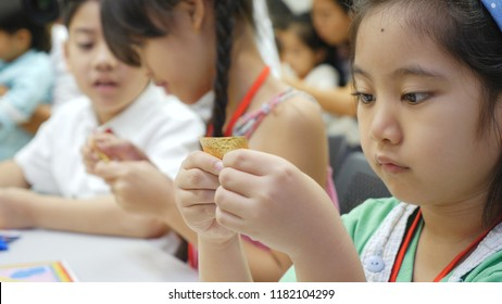 Asian child learning to folding Japanese paper origami, art of paper folding, which is often associated with Japanese culture