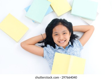 Asian child lying on the floor with books