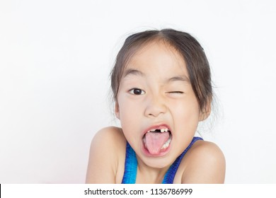 asian child make funny face with her dropped primary tooth