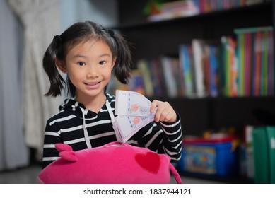 Asian child, managing finances, putting money in a piggy bank
