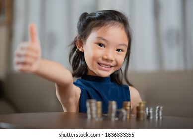 Asian child, managing finances, thumbs up