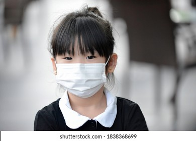 Asian child with mask.Young kid with facemask in the oudoor restaurant setting.Little Chinese girl with face protection during social distancing.