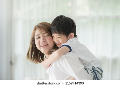 Asian child on a piggy back ride with his mother at home
