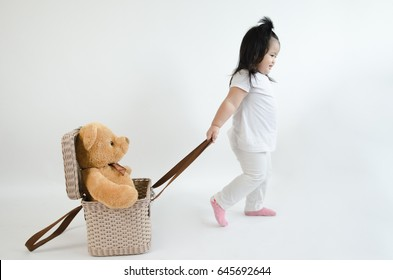 Asian child play pull bear doll in the basket