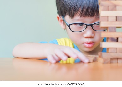 A asian child playing wood blocks stack game, learning and development background concept