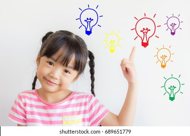 asian child point upper and smile happily on white background with some colorful picture of the electric bulbs ,mean that she got some ideas