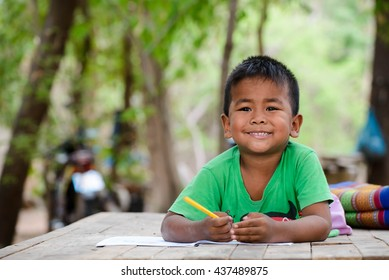 Asian child (poor kids) study at old home.Asia boy learning to drawing,painting with color pencil. Homeless child,smile,lying on dirty wooden table and writing on books.Poor Quality Education Concept.