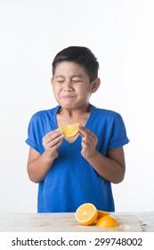Asian child with a pout biting sour lemon. Sour taste.
