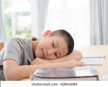 Asian child of primary school age do homework. The boy does his homework at his desk at home. The student / pupil has been bored on the lesson. Child fell asleep during homework