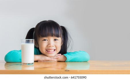 asian child rest her chin on her hands on the wooden table and smile behind a glass of milk