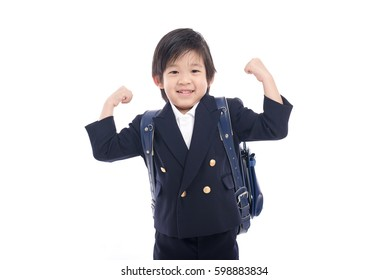 Asian child in school uniform with blue school bag on white background isolated