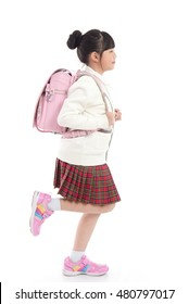 Asian child in school uniform with pink school bag running on white background isolated