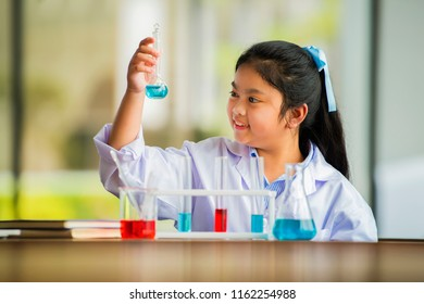 Asian child scientist looking at test tube during a science experiment in class.