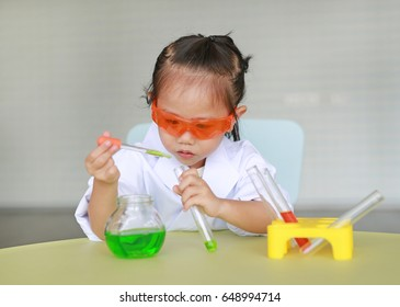 Asian child in scientist uniform holding test tube with liquid, Scientist chemistry and science education concept.