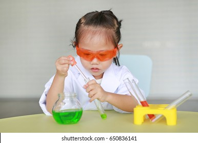 Asian child in scientist uniform holding test tube with liquid