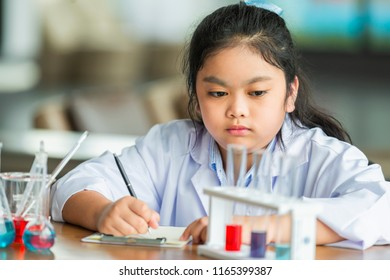 Asian child scientist writing result the test in laboratory room. Scientific research