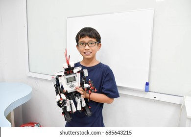 The Asian child show his robot that he made it up.