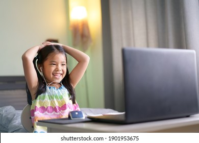 Asian child student or kid girl smile enjoy e-learning on computer notebook with wearing headphone for communication and study online or learn from home to play laptop for education by back to school