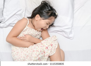 asian child suffering from stomachache and lying on bed. diarrhea or healthy concept