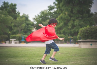 Asian child in in Superhero's costume playing in the park