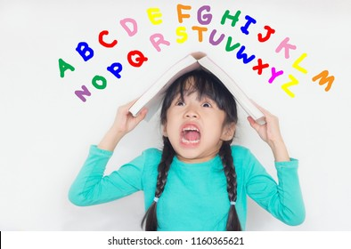 asian child take a book on her head and scream with colorful alphabets on white background