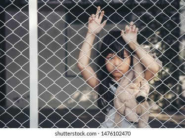 Asian child touchy or kid girl angry cry with sad or have problems and bend down the head lonely. Neglected lonely child against the cage. Little girl crying in house. Violence concept
