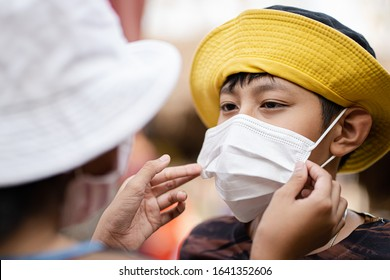 Asian child tourist wearing mask prevent dust PM2.5, novel coronavirus (2019-nCoV), toxic fumes, toxic gases, carbon dioxide in city.