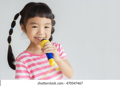 asian child use microphone sing the song , pretend to be the singer