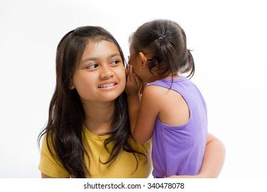 Asian Child Whispering Something to Teen Sister Isolated on White
