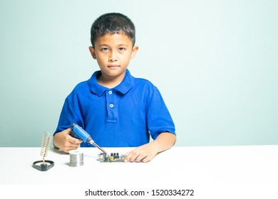 Asian Children age 7-10 is using soldering iron to repair circuit board on white table, concept of children learning and working as technician.