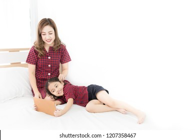 asian children bolster on mother lab, they looking tablet computer in bedroom, they smiling and feeling happy, family time